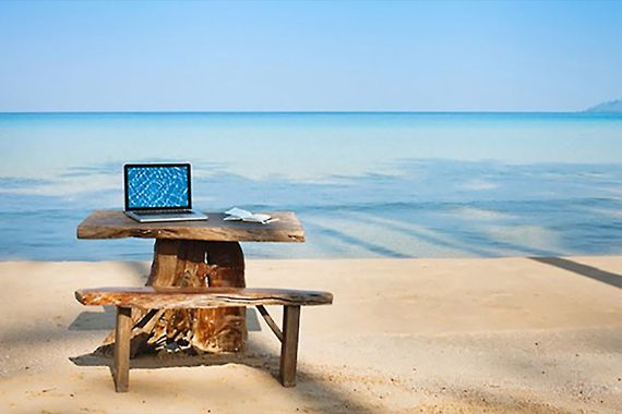 Photo of a rough-hewn desk with an open laptop on it on a beach with the ocean in front of it.